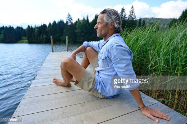germany, mittenwald, mature man relaxing on jetty at lake - blue shorts stock pictures, royalty-free photos & images