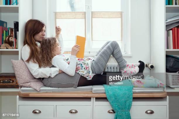 Tyskland mor och dotter på en bänk inomhus en bok