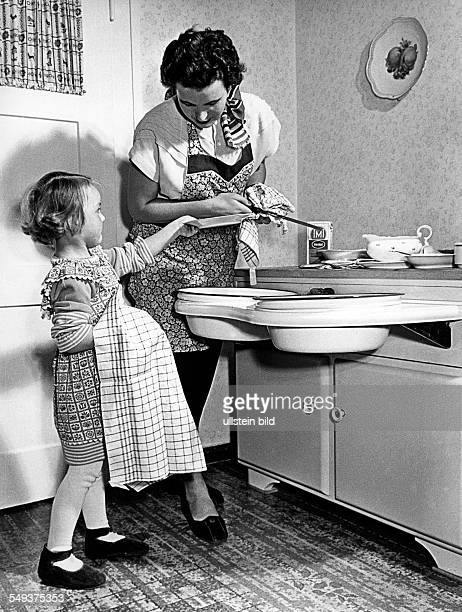 Mother and dughter doingt the dishes in the kitchen Early fifties