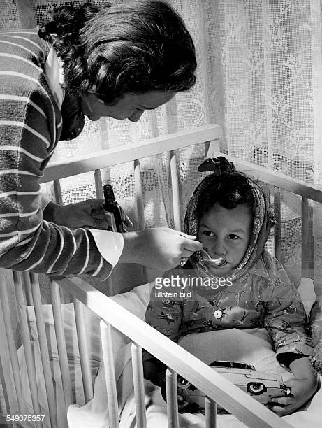 Mother delivers a spoonful of medicin to her child fallen ill with mumps in the fifties