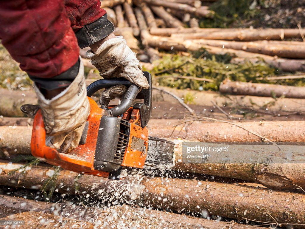 Germany, Muehlenbach, loggers hands sawing tree trunk with motor saw : Stock Photo
