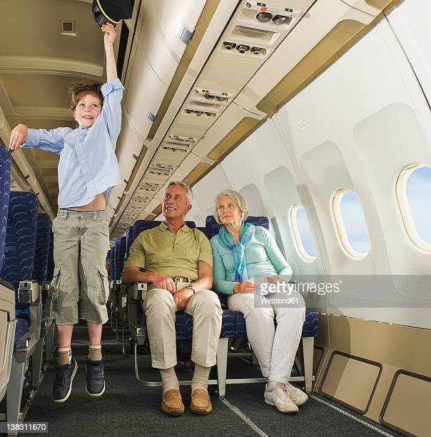 Germany, Munich, Bavaria, Boy jumping with captains hat and senior people looking in economy class airliner