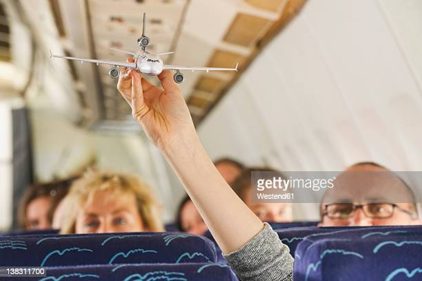 Germany, Munich, Bavaria, Hand showing aeroplane model in economy class airliner
