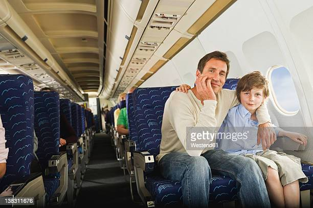Germany, Munich, Bavaria, Man and boy sitting together in economy class airliner