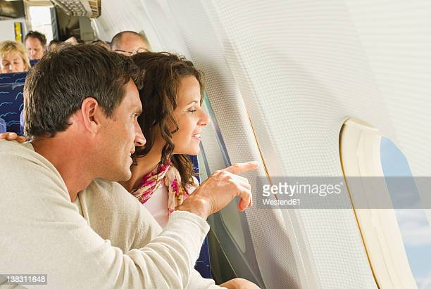 Germany, Munich, Bavaria, Man and women looking out through window in economy class airliner