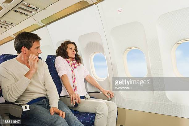Germany, Munich, Bavaria, Mid adult couple looking out through window and getting scared in economy class airliner