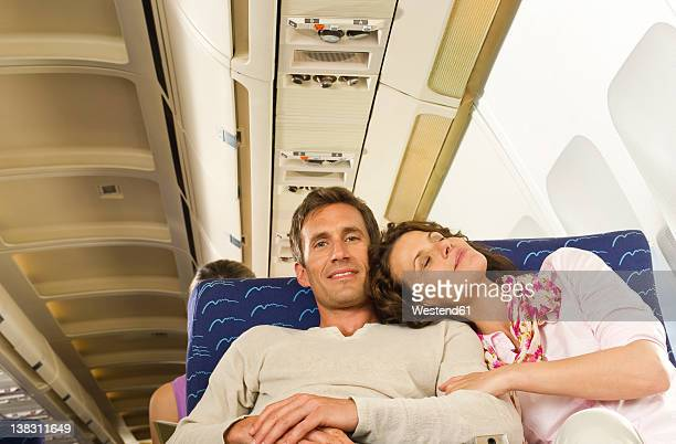Germany, Munich, Bavaria, Mid adult couple relaxing in economy class airliner