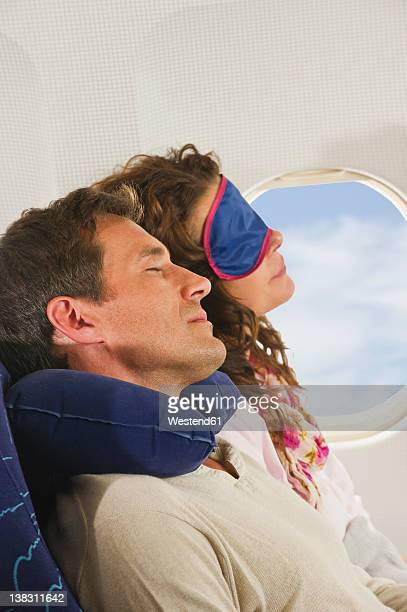 Germany, Munich, Bavaria, Mid adult couple wearing sleep mask and sleeping in economy class airliner