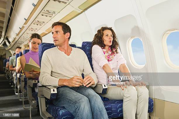 Germany, Munich, Bavaria, Passengers reading book in economy class airliner
