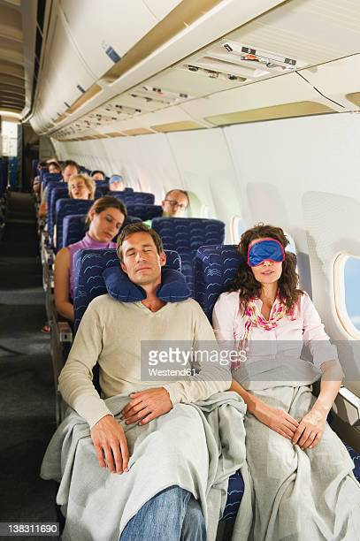 Germany, Munich, Bavaria, Passengers sleeping in economy class airliner