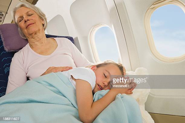 Germany, Munich, Bavaria, Senior woman and girl sleeping beside window in economy class airliner