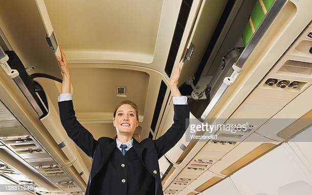 Germany, Munich, Bavaria, Stewardess closing safety lockers in economy class airliner
