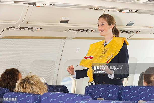 Germany, Munich, Bavaria, Stewardess guiding passengers with life vest in economy class airliner