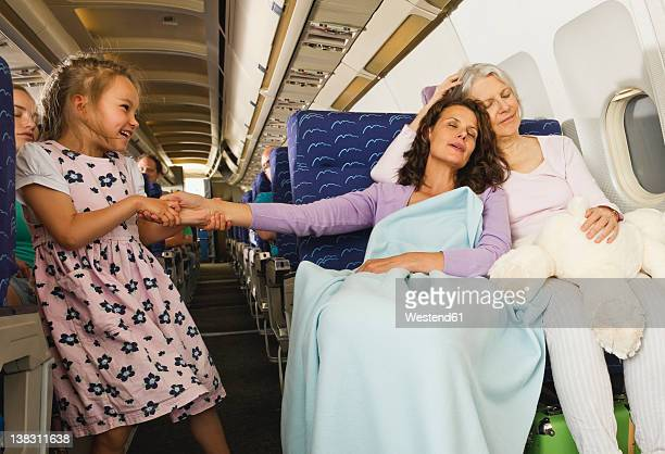 Germany, Munich, Bavaria, Women sleeping and girl pulling woman's hand in economy class airliner