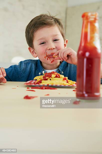 Germany, Munich, Boy eating French fries with ketchup