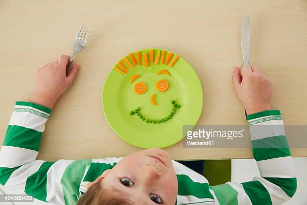 Germany, Munich , Boy eating peas and carrots showing anthropomorphic face