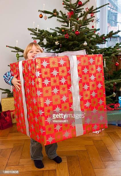 Germany, Munich, Boy holding big christmas present