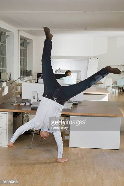 germany, munich, businessmen in office, one of them doing cartwheel - cartwheel stock pictures, royalty-free photos & images