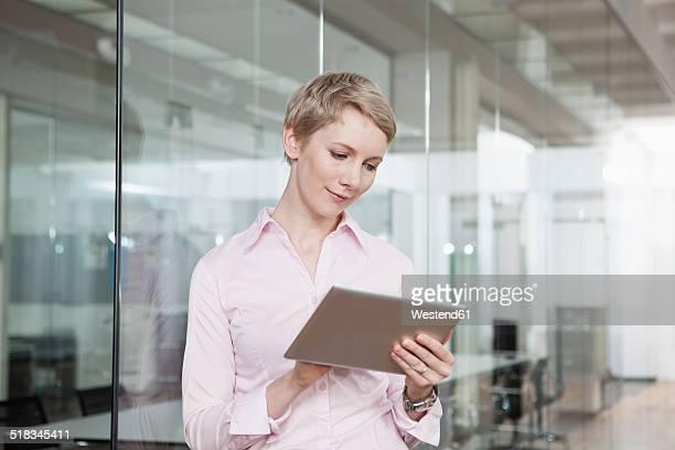 Germany, Munich, Businesswoman in office, using digital tablet