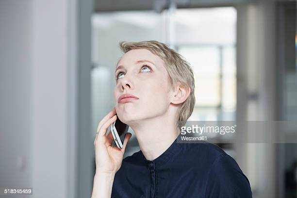 germany, munich, businesswoman in office, using smart phone - wachten stockfoto's en -beelden