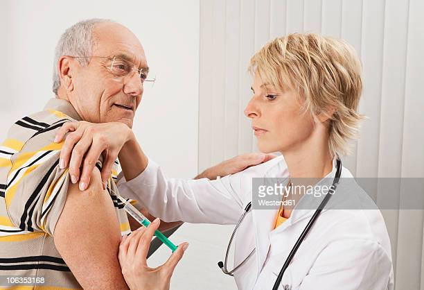 Germany, Munich, Doctor injecting man