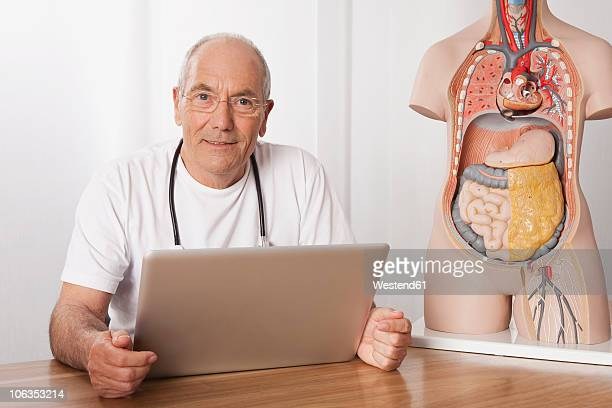 Germany, Munich, Doctor with laptop and human body figurine