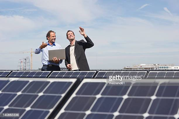 germany, munich, engineer and man discussing in solar plant - crane construction machinery stock pictures, royalty-free photos & images
