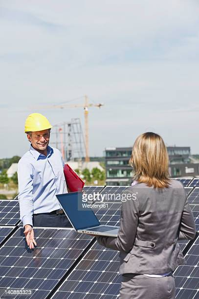 Germany, Munich, Engineers with laptop and discussing in solar plant