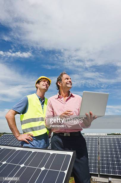 Germany, Munich, Engineers with laptop in solar plant