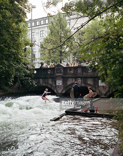 Germany, Munich, Englischer Garden, surfer riding Eisbach River wave