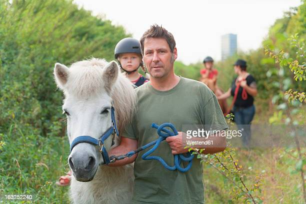 Germany. Munich, Experiental educators with children guiding horse ride in suburbs