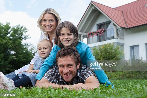 Germany, Munich, Family in front of house, smiling, portrait