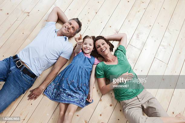 Germany, Munich, Family lying on floor, smiling