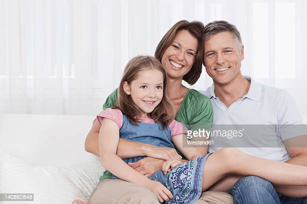 Germany, Munich, Family sitting on couch, smiling