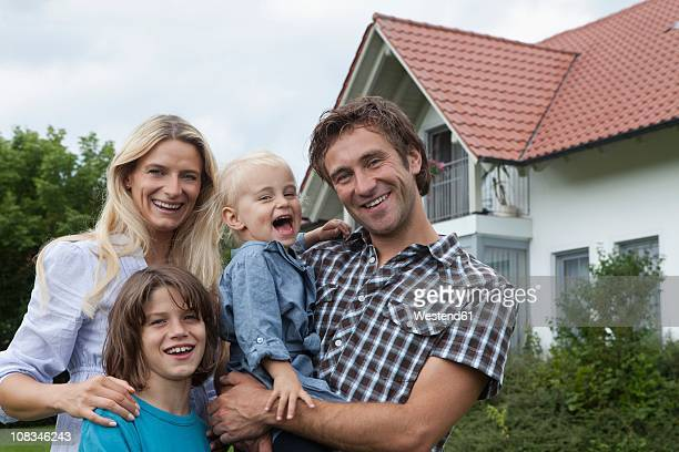 Germany, Munich, Family standing in front of house, smiling, portrait