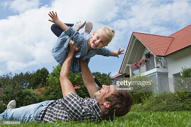 Germany, Munich, Father playing with daughter (2-3 Years) in garden