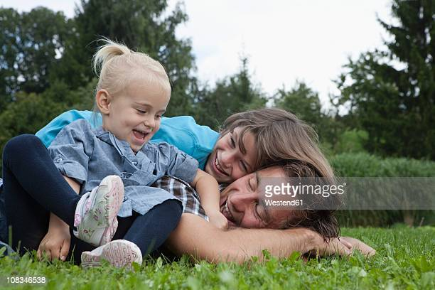Germany, Munich, Father with children in garden, smiling