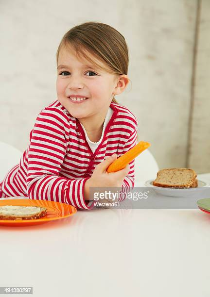Germany, Munich, Girl sitting at table with carrot and wholemeal bread on plate
