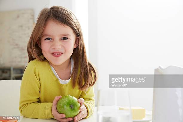germany, munich, girl sitting at table with green apple - kid girl eating apple stock photos and pictures