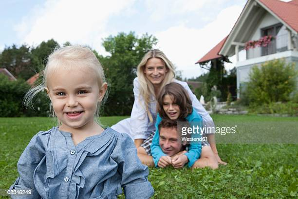 Germany, Munich, Girl (2-3 Years) smiling with family in background