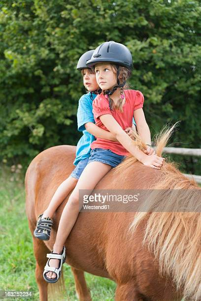Germany, Munich, Girls learning to ride horse in children's camp