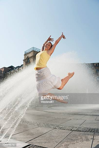 Germany, Munich, Karlsplatz, Young woman jumping in the air