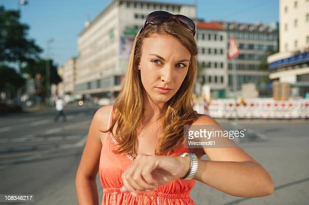 germany, munich, karlsplatz, young woman seriously looking away - impaciente fotografías e imágenes de stock