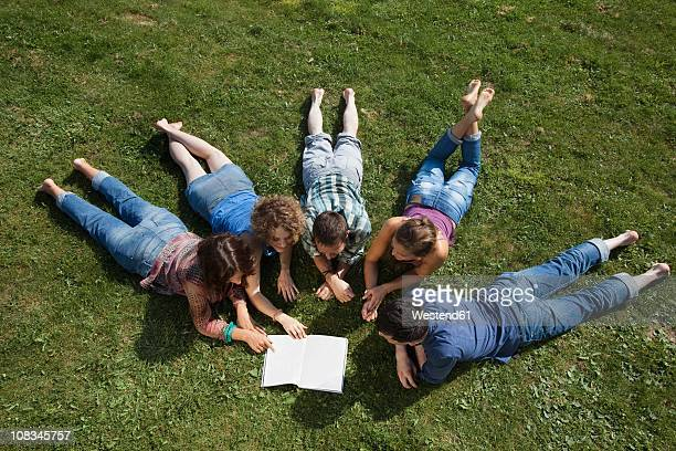 Germany, Munich, Man and woman lying on grass and reading book