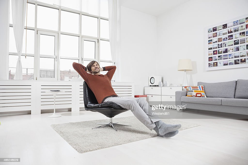 Germany, Munich, Man at home, sitting in chair, hands behind head : Stock Photo