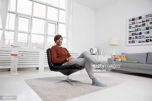 Germany, Munich, Man at home, sitting in chair