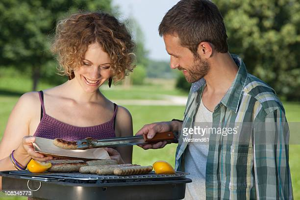 germany, munich, man serving sausage in plate, woman smiling - snag tree stock pictures, royalty-free photos & images