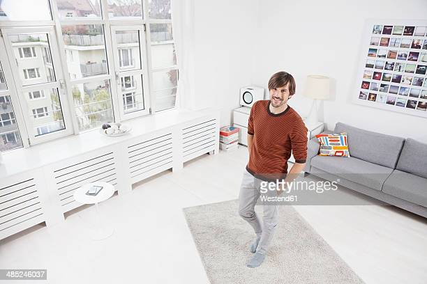 Germany, Munich, Man standing on carpet, hands in pockets