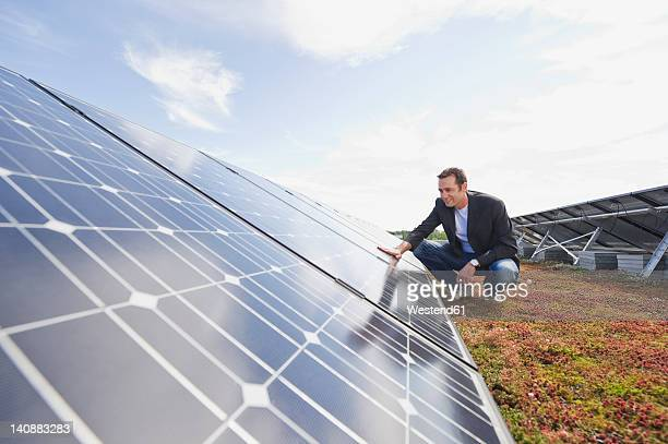 Germany, Munich, Man touching solar panel in solar plant