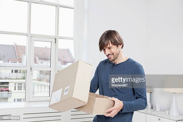 germany, munich, man unpacking cardboard box - recebendo - fotografias e filmes do acervo